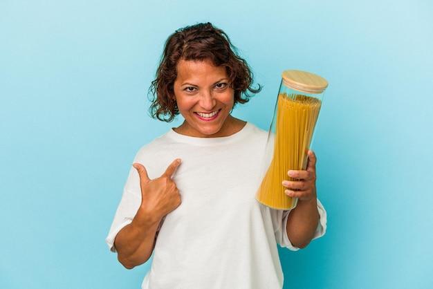 誘うようにあなたに指で指している青い背景に分離されたパスタ瓶を保持している中年のラテン女性が近づいています。 Premium写真