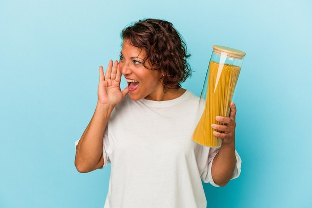 開いた口の近くで叫び、手のひらを保持している青い背景で隔離のパスタ瓶を保持している中年ラテン女性。