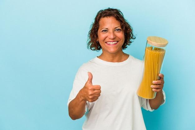 笑顔と親指を上げる青い背景で隔離のパスタ瓶を保持している中年ラテン女性