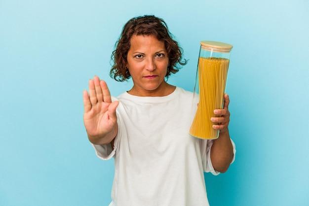 一時停止の標識を示す伸ばした手で立っている青い背景に分離されたパスタ瓶を保持している中年のラテン女性は、あなたを防ぎます。