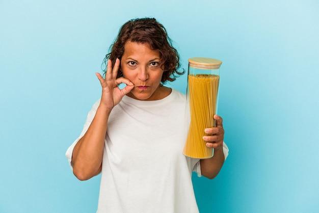 秘密を保持している唇に指で青い背景に分離されたパスタ瓶を保持している中年ラテン女性。
