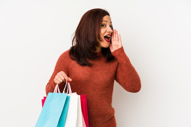 Middle age latin woman holding a shopping bags isolated shouting and holding palm near opened mouth.
