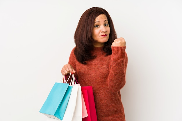 Middle age latin woman holding a shopping bags showing fist to camera, aggressive facial expression.