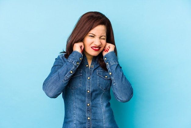 Middle age latin woman isolated on a blue background covering ears with hands.