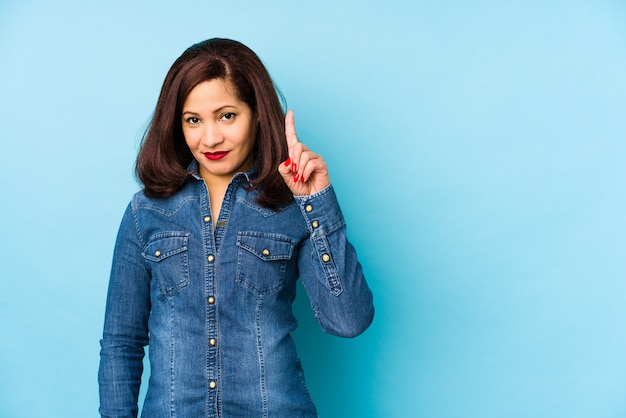 Middle age latin woman isolated on a blue wall showing number one with finger.