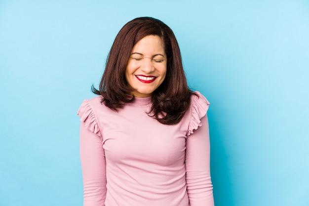 孤立した中年ラテン女性は笑って目を閉じ、リラックスして幸せを感じます。