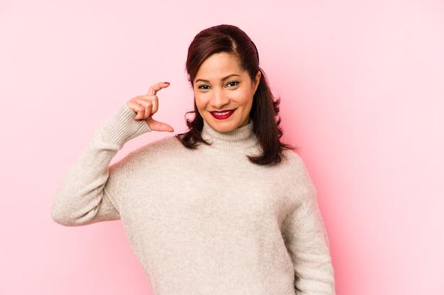 작은 집게 손가락으로 뭔가 들고 웃 고 자신감 핑크에 고립 된 중간 나이 라틴 여자.