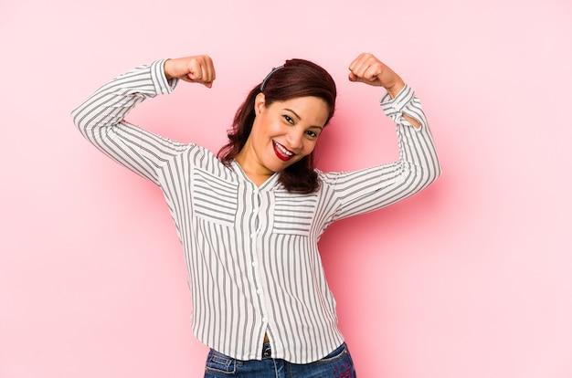 Латинская женщина среднего возраста изолирована на розовом пространстве, показывая жест силы руками, символ женской силы