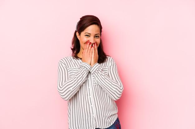 뭔가 대해 웃고, 손으로 입을 덮고 분홍색 벽에 격리 된 중년 라틴 여자.