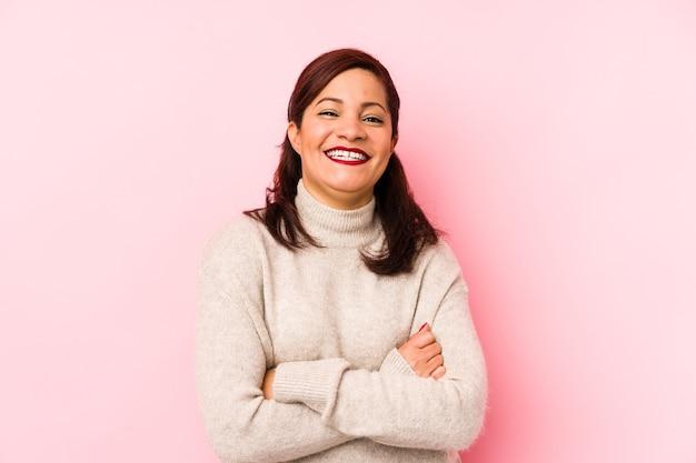 웃으면 서 재미 분홍색 벽에 고립 된 중간 나이 라틴 여자.