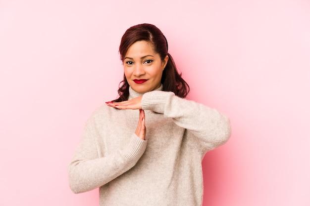 Латинская женщина среднего возраста, изолированные на розовой стене, показывая жест тайм-аута.