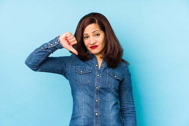 嫌いなジェスチャーを示し、親指を下に向けて青で隔離された中年のラテン女性。不一致の概念。