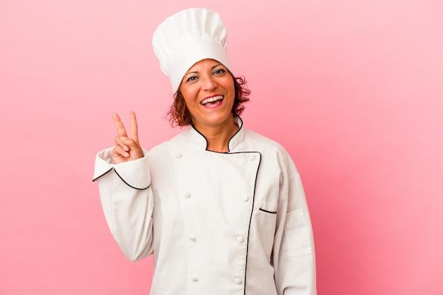 ピンクの背景に分離された中年のラテン女性は、指で平和のシンボルを示して楽しくてのんきです。