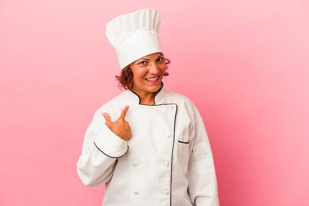 Латинская женщина среднего возраста изолирована на розовом фоне, указывая пальцем на вас, как будто приглашая подойти ближе.
