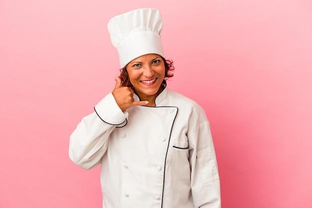 指で携帯電話の呼び出しジェスチャーを示すピンクの背景に分離された中年ラテン女性。