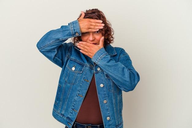 白い背景で隔離された中年のラテン女性は、恥ずかしい顔を覆って、指を介してカメラで点滅します。