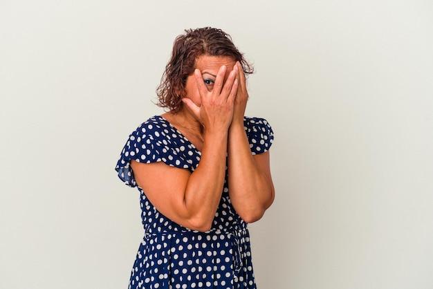 白い背景で隔離された中年のラテン女性は、おびえ、神経質な指を点滅します。