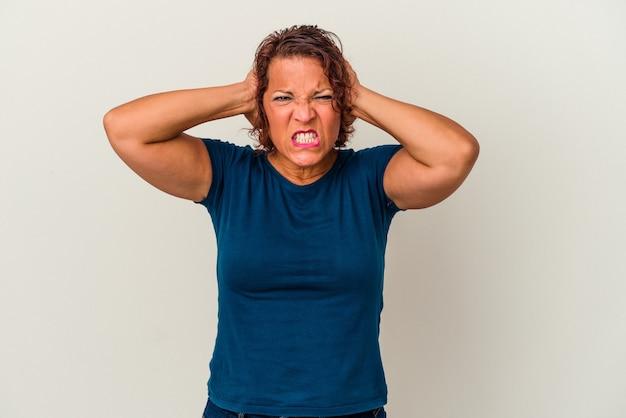 中年のラテン女性は、あまりにも大きな音を聞かないように手で耳を覆う白い背景で隔離。
