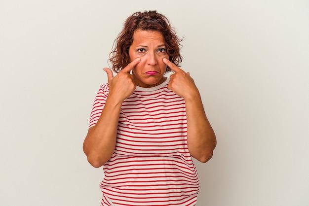 Латинская женщина среднего возраста, изолированные на белом фоне, плачет, недовольна чем-то, агонией и концепцией замешательства.