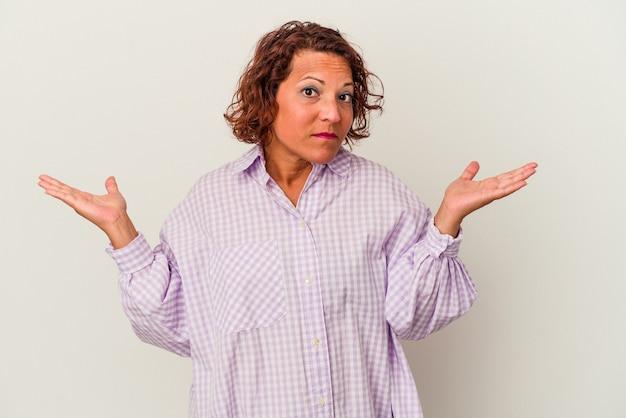 ジェスチャーを疑って肩をすくめる白い背景に分離された中年のラテン女性。