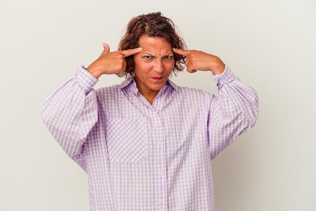 Латинская женщина среднего возраста, изолированные на белом фоне, сосредоточилась на задаче, держа указательные пальцы, указывая головой.