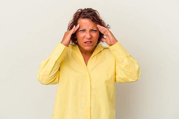 顔の正面に触れて、頭痛を持っている白い背景で隔離された中年のラテン女性。