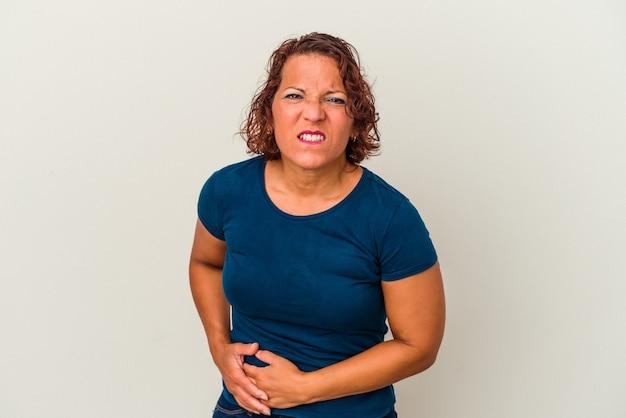 肝臓の痛み、胃の痛みを持っている白い背景で隔離の中年ラテン女性。