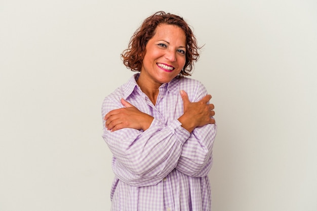 白い背景の抱擁に分離された中年のラテン女性は、のんびりと幸せに笑っています。