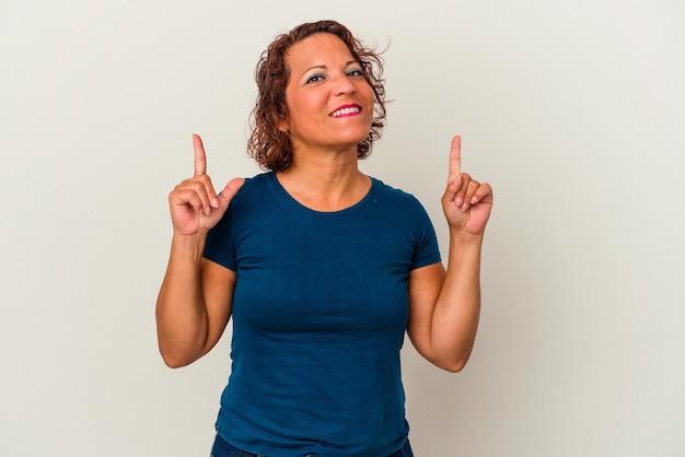흰색 배경에 격리된 중년 라틴 여성은 두 앞 손가락으로 빈 공간을 표시함을 나타냅니다.