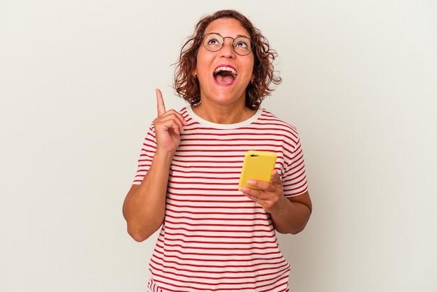口を開けて逆さまを指している白い背景に分離された中年ラテン女性。