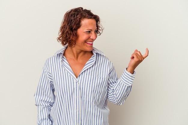 招待が近づくようにあなたに指を指している白い背景に分離された中年のラテン女性。