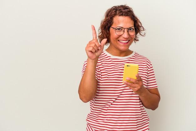 指でナンバーワンを示す白い背景で隔離の中年ラテン女性。