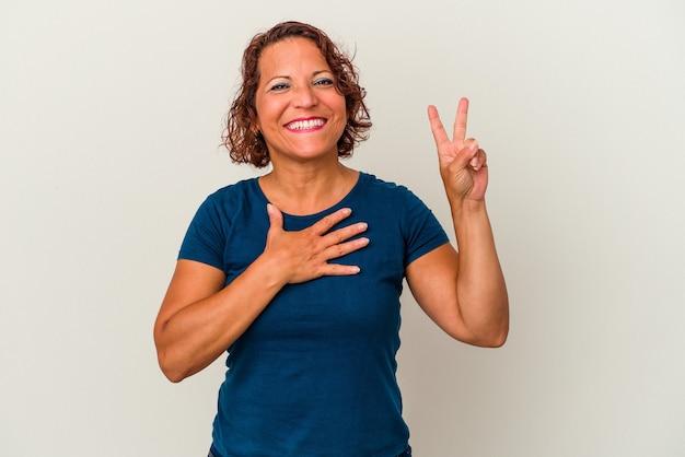 誓いを立て、胸に手を置いて、白い背景で隔離される中年ラテン女性。 Premium写真