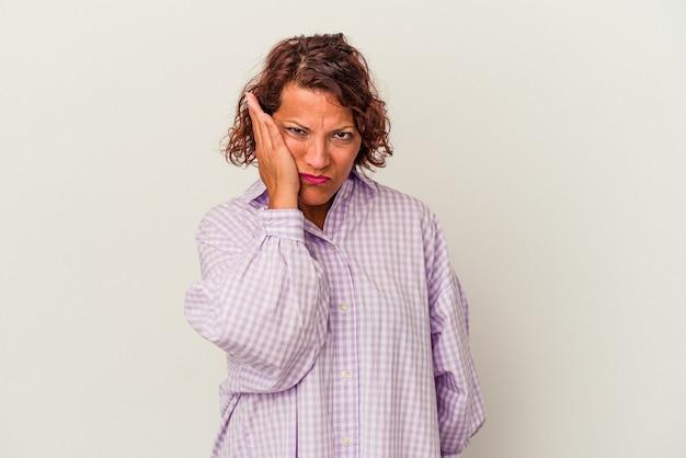 白い背景で隔離された中年のラテン女性は疲れていて、頭に手を置いて非常に眠いです。