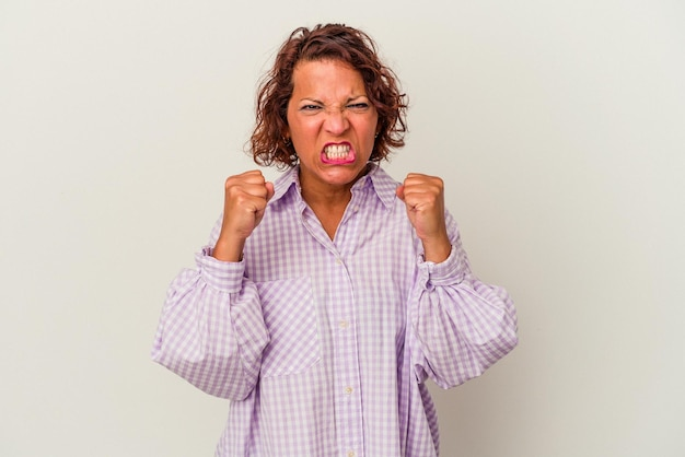 白い背景で隔離された中年ラテン女性は緊張した手で叫んで動揺します。