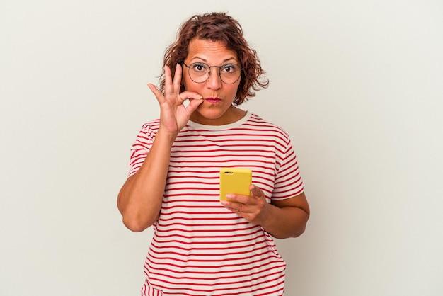Латинская женщина среднего возраста, изолированные на белом фоне с пальцами на губах, сохраняя в секрете.
