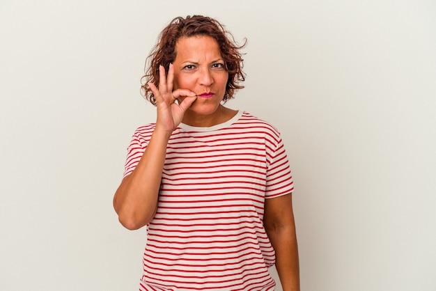 秘密を保持している唇に指で白い背景に分離された中年ラテン女性。