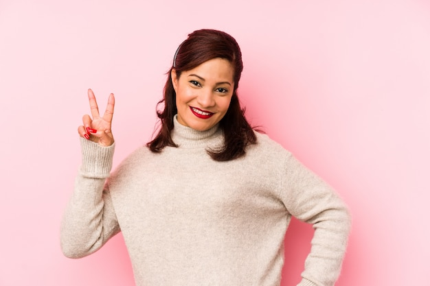 Middle age latin woman isolated on a pink background joyful and carefree showing a peace symbol with fingers.
