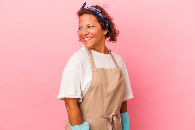 Middle age latin woman isolated on pink background looks aside smiling, cheerful and pleasant.