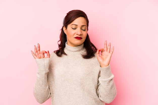Middle age latin woman isolated on a pink background relaxes after hard working day, she is performing yoga.