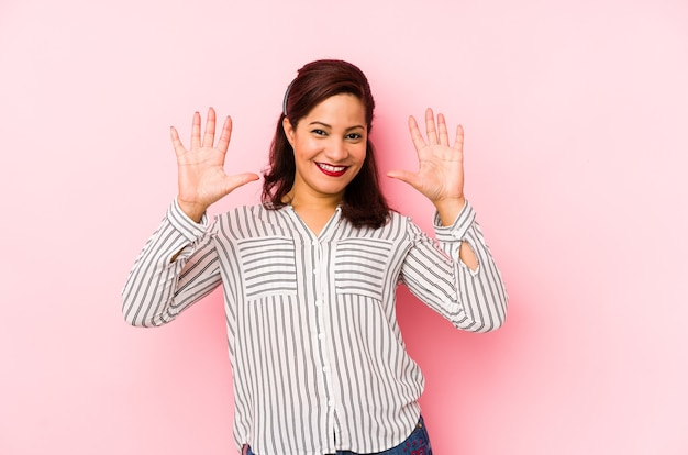 Middle age latin woman isolated on pink showing number ten with hands.
