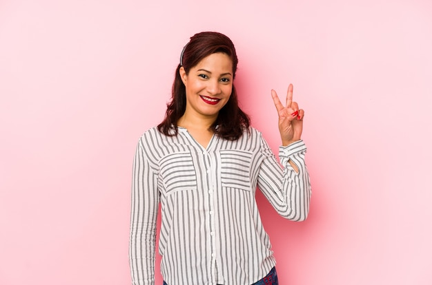 Middle age latin woman isolated on a pink wall showing victory sign and smiling broadly.