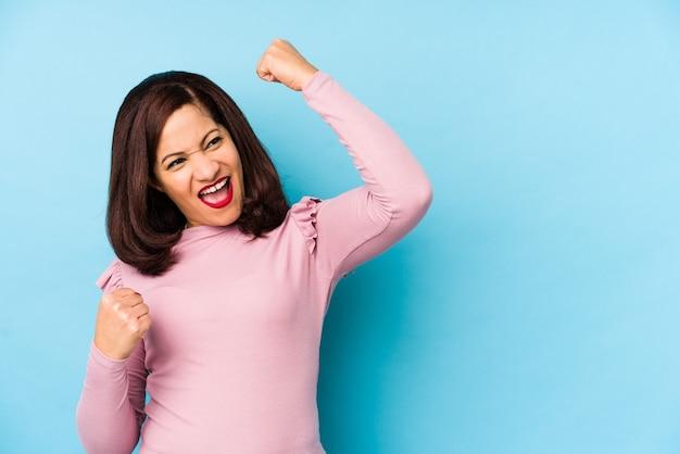 Латинская женщина среднего возраста изолировала поднимающий кулак после победы, концепции победителя.