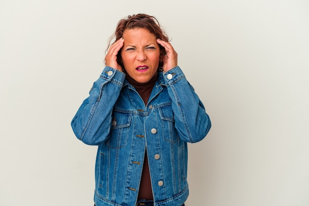 Middle age latin woman isolated on white background covering ears with fingers, stressed and desperate by a loudly ambient.