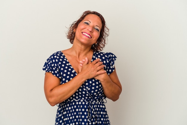 Middle age latin woman isolated on white background has friendly expression, pressing palm to chest. love concept.