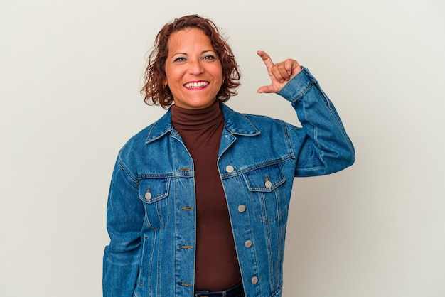 Middle age latin woman isolated on white background holding something little with forefingers, smiling and confident.