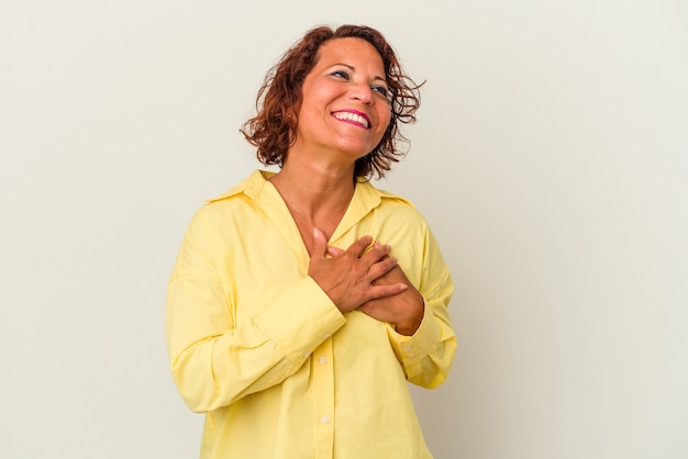 Middle age latin woman isolated on white background laughing keeping hands on heart, concept of happiness.