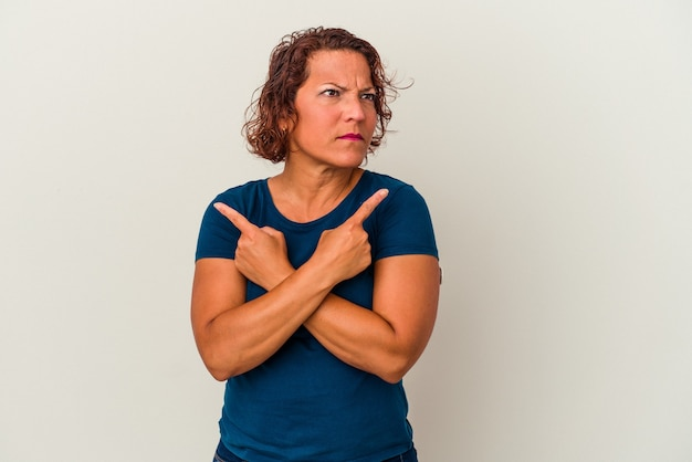 Middle age latin woman isolated on white background points sideways, is trying to choose between two options.