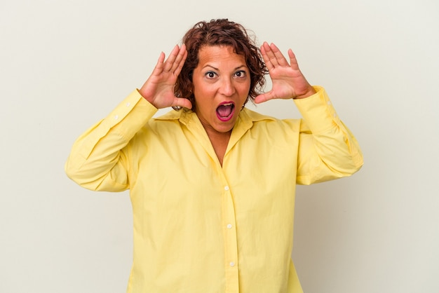 Middle age latin woman isolated on white background receiving a pleasant surprise, excited and raising hands.