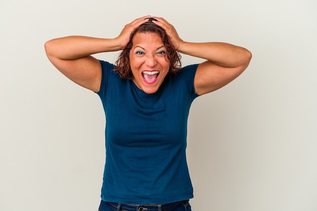 Middle age latin woman isolated on white background screaming, very excited, passionate, satisfied with something.